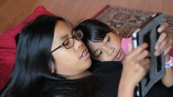 A teenage Asian girl reads a book to her cute little sister using her new digital tablet in the living room.