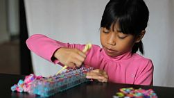 A cute little 8 year old Asian girl has fun making colorful bracelets on her rainbow loom.