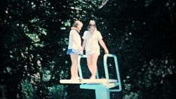 Two girls play around on the diving board of the new backyard swimming pool in the summer of 1967.
