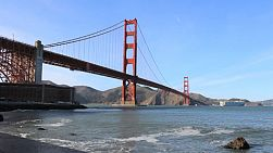 A tilt up shot of waves pounding the coastline under the famous Golden Gate bridge on a gorgeous sunny day in San Francisco, California.