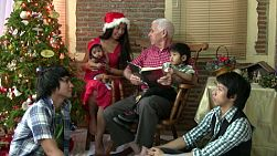 A grandfather reads the Christmas story to his Asian grandsons while his family listens attentively.