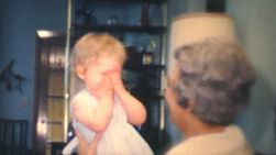 A grandmother spends time playing peek-a-boo with her new granddaughter in 1970.