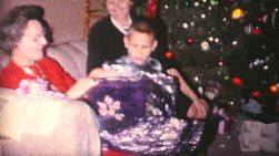 A grandmother enjoys opening Christmas presents with her family on Christmas morning in 1962.