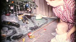 A wonderful festive scene with Grandma and grandson enjoying the new model railroad train set by the Christmas tree in 1963.