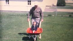 A proud grand father pushes his granddaughter around the back yard in a wheelbarrow in the summer of 1970.