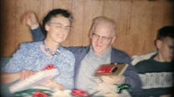 Cute grandparents share a tender kiss after exchanging Christmas gifts on Christmas morning in Akron, Ohio in 1963.