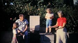 Grandparents playing around with their grandkids on the new outdoor barbecue pit during the summer of 1961.