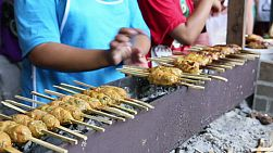 Two men grilling BBQ chicken on a stick over hot coals on the streets of Bangkok, Thailand.