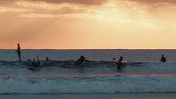 Group of surfers surfing at South Cottesloe Beach in Western Australia, as the sun sets in the background.