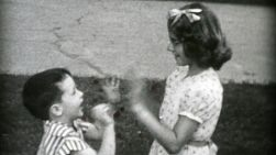 A handsome young boy standing next to vintage old car smiles at the camera in the summer of 1955 and then plays with older sister.