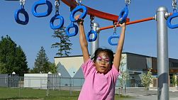 A cute little 9 year old Asian girl with her face painted enjoys the challenge of climbing on the playground structure.