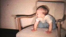 A cute little baby boy has fun rocking himself on an old rocking chair.