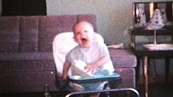 A cute baby boy has a great time in his walker laughing and smiling and having fun.