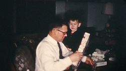 A happy Dad enjoys opening his gifts on Christmas Day in 1958!