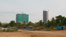 PATTAYA, THAILAND - AUGUST 2015: Handheld view across a vacant lot to two high rise buildings being built in the background.