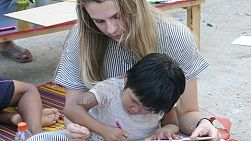 A high school student lovingly helps a cute Thai girl color her page during an English class in Pattaya, Thailand.