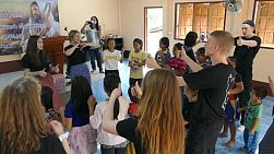 A group of high school students on an overseas missions trip sing action songs to kids in Pattaya, Thailand during an English Camp.