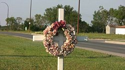 A white cross with a flower wreath hanging on it stand by the side of the highway.