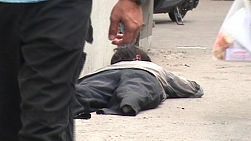A homeless amputee lays on a sidewalk in Bangkok, Thailand hoping that someone will give money, help or assistance.