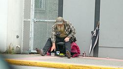 An old homeless man living on the streets checks his coin jar after begging on the streets of Vancouver, BC.