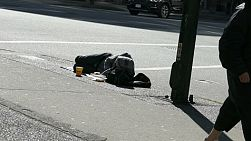 A homeless man lays on a busy street in downtown Vancouver waiting for donations and food.