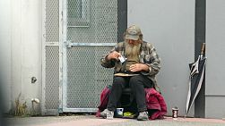 VANCOUVER, BC, OCTOBER 2015: An old homeless man living on the streets prepares to roll a cigarette while waiting for donations on the streets of Vancouver, BC.