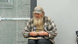 VANCOUVER, BC, OCTOBER 2015: An old homeless man living on the streets rolls a cigarette while waiting for donations on the streets of Vancouver, BC.