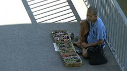 An elderly handicapped Asian man tries to sell some items on a walkway in downtown Bangkok, Thailand.