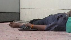 A close up shot of a homeless man sleeping on the sidewalk in Bangkok, Thailand.