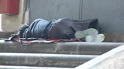 A homeless man sleeping on the road with traffic passing by.