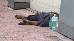 A homeless man sleeps on a sidewalk in the midday sun in Bangkok, Thailand.