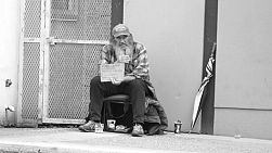 VANCOUVER, BC, OCTOBER 2015: An old homeless man living on the streets smokes a cigarette while waiting for donations on the streets of Vancouver, BC.