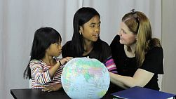 A pretty housewife uses a globe to help teach her two Asian daughters an important geography lesson.