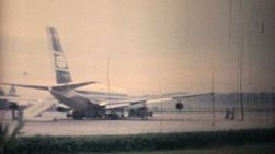 A shot of the Hong Kong Airport with a plane on the tarmac and then flying to Bangkok, Thailand in 1958.