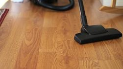 A housewife uses a vacuum to clean the floor in her home.