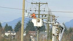 A hydro repair lineman in an orange jumpsuit and hard hat repairs a problem on the line in the city of Vancouver.