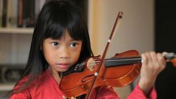 An intense little 6 year old Asian girl plays her violin in the living room.