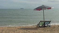 A couple of lonely beach chairs invite tourists to come and relax on the beach in Pattaya, Thailand.