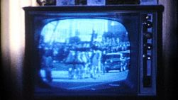 A family watches the funeral procession of President Kennedy and his horse drawn carriage on TV in November 1963.