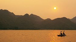 Two kayakers paddling by, one towing the other, in front of a view of the sun setting behind mountains from across the Mae Klong River in Kanchanaburi, Thailand, on a hazy day.