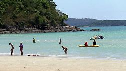People enjoying kayaking and boating on a beautiful ocean beach in Sattahip, Thailand.