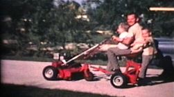 A loving dad takes his two young children on a fun adventure riding on his new riding lawn mower.