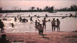 A shot of a crowded beach with tons of kids playing in the water and then a little boy runs towards the camera.