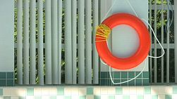 A life saving ring hangs by the side of an indoor pool ready to be put into action. (HD 1080p30)