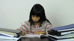 A little Asian girl finally finishes all her homework from school.