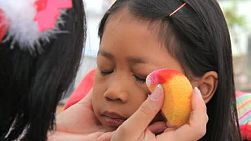 A cute little 6 year old Asian girl has her eyes painted as she waits for her face painting mask.