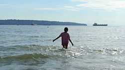 A cute little 9 year old Asian girl enjoys jumping in the waves in English Bay near Stanley Park in Vancouver, BC.