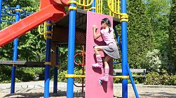 A cute little 9 year old Asian girl enjoys the challenge of doing some rock climbing at the playground.