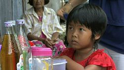 A cute little Thai girl waits patiently for a sweet ice snack from a local vendor in the slums.