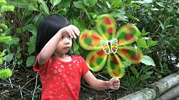 A cute little Thai girl spins a colorful butterfly pinwheel in the school playground.